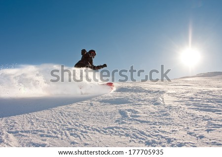 Teenage boy riding a snowboard downhill in sunny weather, spraying snow as he turns - stock photo