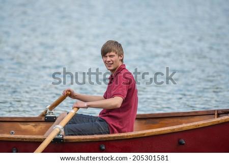Teenage boy rowing a boat on a lake - stock photo