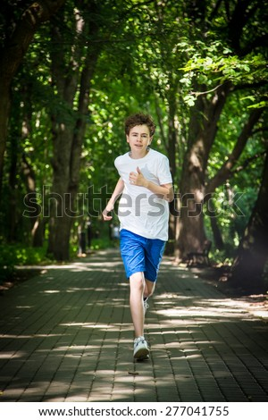 Teenage boy running in park  - stock photo