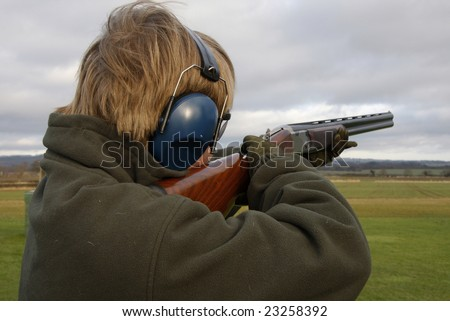 Teenage boy shooting at the clay pigeon - stock photo
