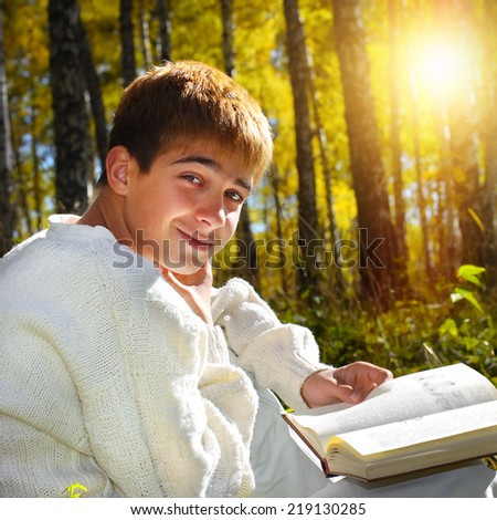 Teenage Boy sit in the Forest with a Book - stock photo