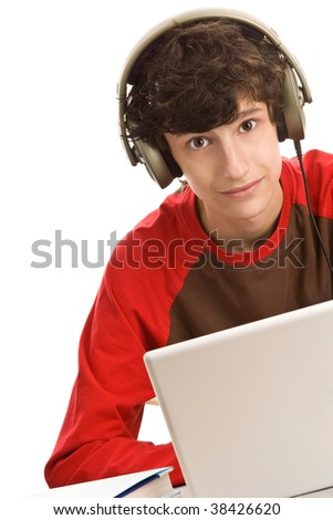 Teenage boy sitting behind desk with laptop computer listening to music isolated on white background - stock photo
