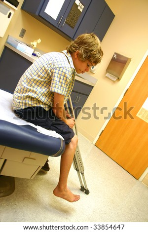 Teenage boy sitting on an examining table holding his crutches as he awaits the doctor's arrival. - stock photo