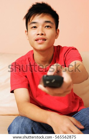 Teenage boy sitting on sofa, pointing remote control towards camera