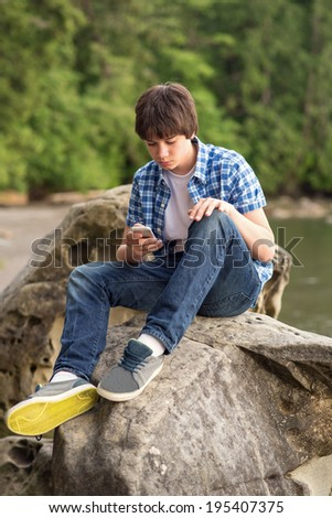 Teenage boy sitting on the rock using his smart-phone. - stock photo