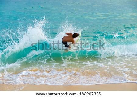 Teenage boy skim boarding on the tropical island of Maui, Hawaii, USA - stock photo