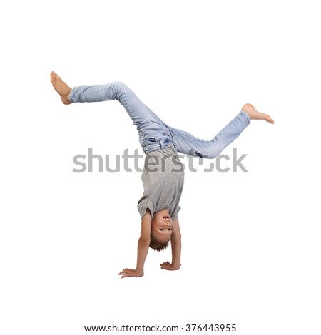 Teenage boy stands on hands brandishing legs in air isolated on white background