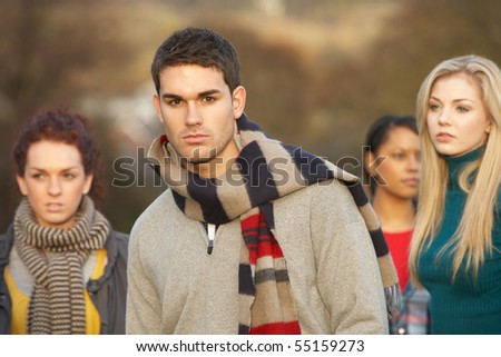 Teenage Boy Surrounded By Friends In Outdoor Autumn Landscape