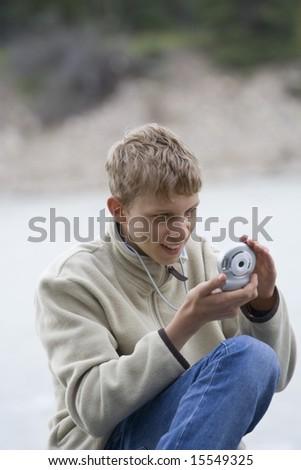 teenage boy taking photos - with a small digital camera - stock photo