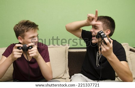 Teenage boy teasing younger brother with loser sign while playing video game - stock photo
