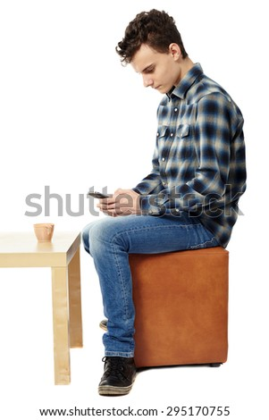 Teenage boy texting using a smartphone isolated on white - stock photo