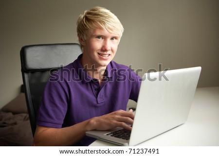 Teenage Boy Using Laptop At Home - stock photo