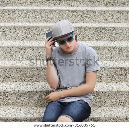 Teenage boy using smart phone - stock photo