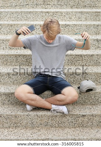 Teenage boy using smart phone.Teenage boy gesturing - stock photo