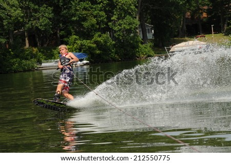 teenage boy wakeboarding behind a ski boat