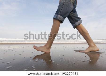 Teenage boy walking on the beach