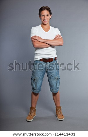 Teenage boy with brown hair and eyes. Wearing white t-shirt and blue shorts. Good looking. Casual wear. Expressions. Studio portrait isolated on grey background.