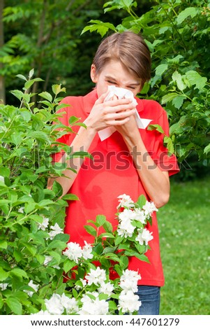 Teenage boy with hay fever blowing his nose allergic to bloom flowers in a spring garden - stock photo