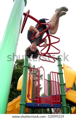 Teenage boy with long hair at playground - stock photo