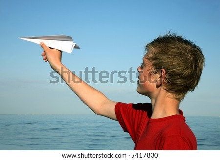 Teenage boy with paper dart - stock photo