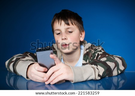 teenage boy with phone in hand on blue background - stock photo