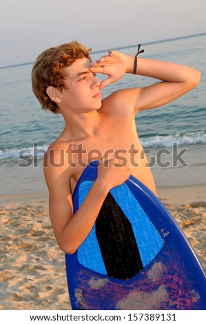 teenage boy with skimboard at the beach - stock photo