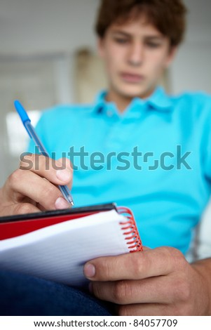 Teenage boy writing in notebook - stock photo