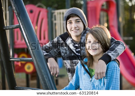 Teenage boy (15 years) with arm around younger sister (11 years) by playground equipment