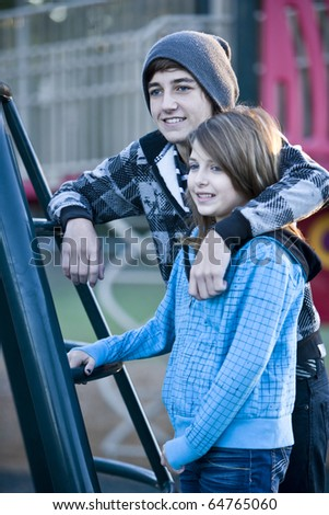 Teenage boy (15 years) with arm around younger sister (11 years) by playground equipment - stock photo