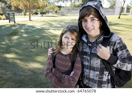 Teenage boy (15 years) with arm around younger sister (11 years), with bookbags at school - stock photo