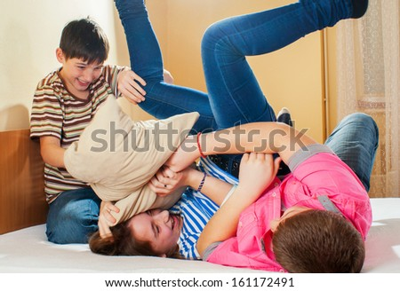 Teenage boys and a girl having pillow fight on the bed. - stock photo