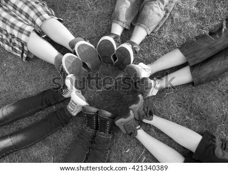 Teenage boys and girls feet and legs touching in circle while sitting on spring meadow on sunny day. - stock photo