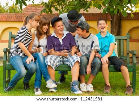 Teenage boys and girls having fun in the garden while sitting on the bench. - stock photo