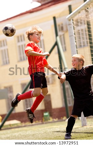 Teenage boys playing soccer at sunny day - stock photo