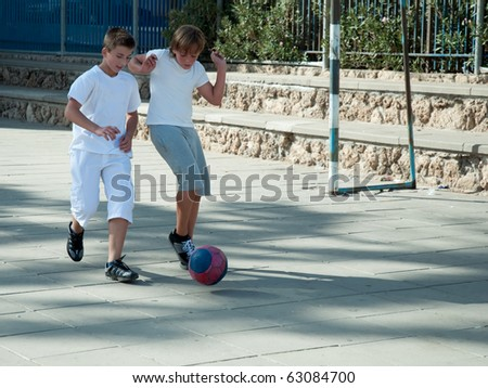 Teenage boys playing soccer at sunny day .