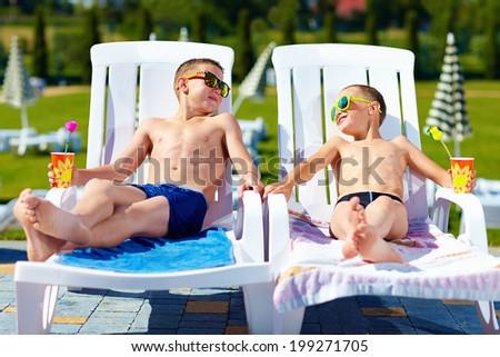 teenage boys relaxing on sunbeds in waterpark - stock photo