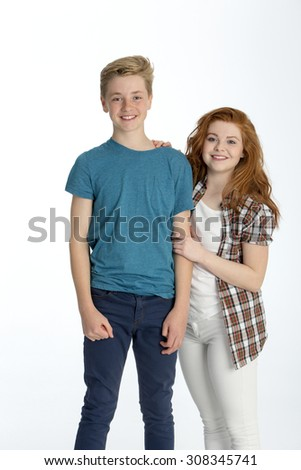 Teenage brother and sister posing together in front of a white background