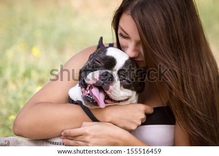 Teenage brunette girl playing with her healthy young bulldog in the park - stock photo