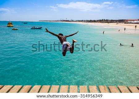 Teenage Cape verdean boy jumping on the turquoise  water of Santa Maria beach in Sal Cape Verde - Cabo Verde - stock photo