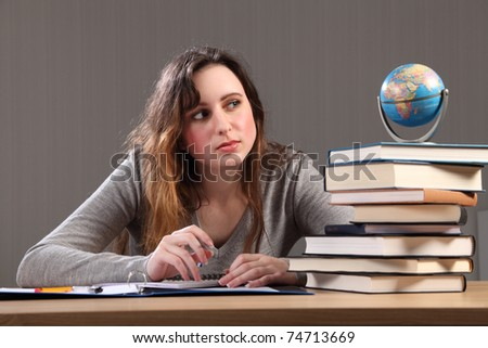 Teenage caucasian student girl at home, sitting to her desk studying the globe for geography homework with work books nearby. - stock photo