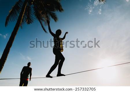 teenage couple balancing on slackline  with sky view on the beach silhouette - stock photo