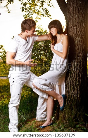 Teenage couple by tree in park - stock photo