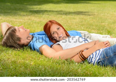 Teenage couple enjoying sun lying together on grass relaxing - stock photo