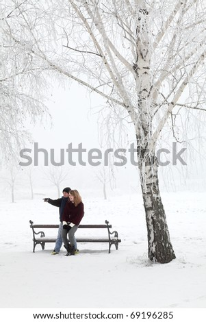 Teenage couple having fun at snow in park