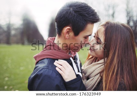 Teenage couple in romantic mood. Affectionate young couple in park.