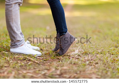teenage couple kissing outdoors at the park - stock photo