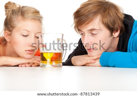 teenage couple leaning on table with beer, white background - stock photo