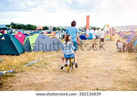 Teenage couple riding bike together at summer music festival - stock photo