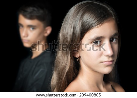 Teenage couple sad and angry at each other on a black background - stock photo