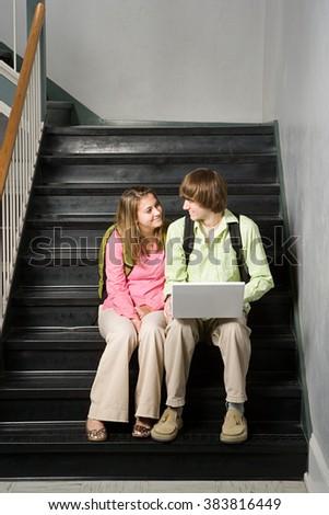 Teenage couple sat on school stairway - stock photo